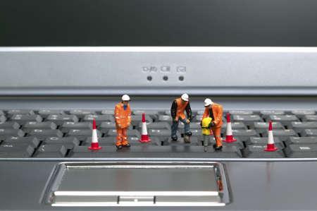Miniature workmen repairing a laptop keyboard.