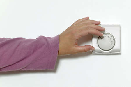 turn: Womans hand turning down the temperature on a room thermostat. Stock Photo