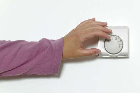 Womans strony obniżenie temperatury w pomieszczeniu termostat.