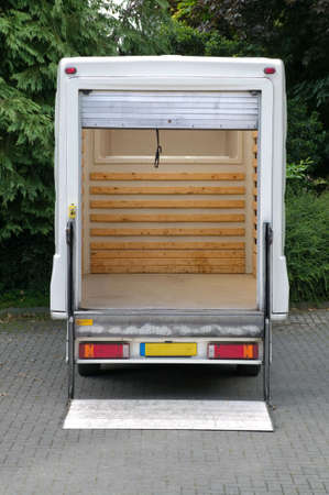 Rear view of an empty white box van with its tail lift lowered. photo