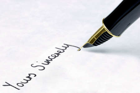sincerely: Yours Sincerely written on watermarked textured paper using a gold nibbed fountain pen. Focal point is on the text.
