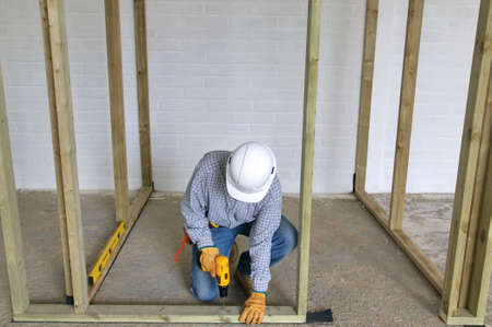 drill floor: Carpenter fixing a timber framework into a concrete floor
