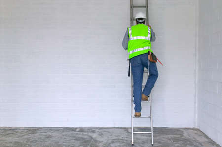 builders: Workman in reflective vest and hard hat climbing a ladder, slight motion blur on the man. Stock Photo