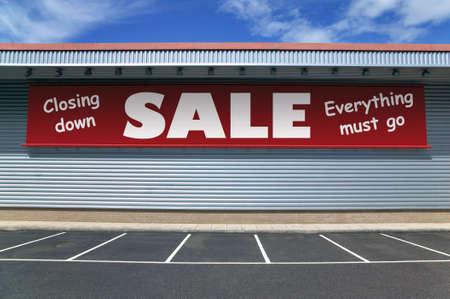 Venta al por menor edificio con una pancarta en el exterior para el cierre de una venta. Buena imagen de la recesión conceptos.