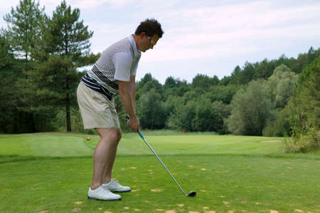 par: Golfer addressing the ball as he is about to tee off with an iron on a short par three Stock Photo