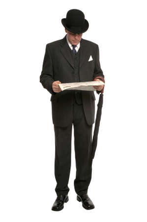stockbroker: Businessman in pinstripe suit and traditional bowler hat with umbrella reading the financial newspaper