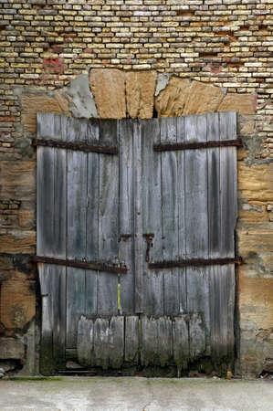 derelict: An old derelict wooden door set in weathered brick wall