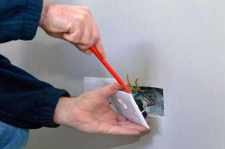 toma corriente: Las manos de un electricista la instalaci�n de una toma de alimentaci�n Foto de archivo