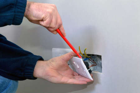 The hands of an electrician installing a power socket photo