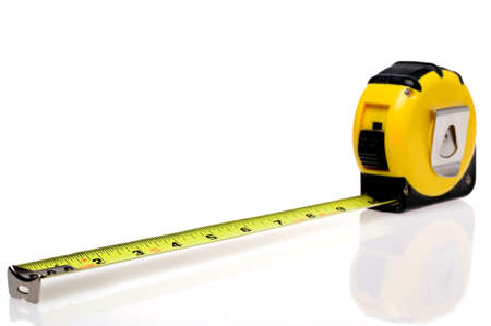A yellow retractable steel tape measure isolated on a white background with slight reflection. Stock Photo