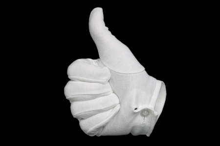 gesticulation: Hand in a white cotton glove gesturing a thumbs up sign, isolated on a black background. Invisible man effect on glove.