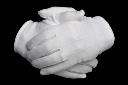 held: Hands held in white cotton gloves isolated on a black background. Stock Photo