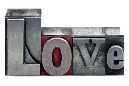 The word Love in old letterpress printing blocks isolated on a white background. Stock Photo