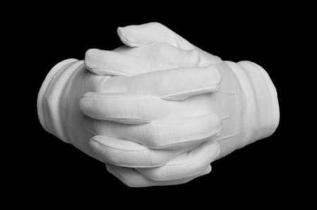 reassurance: Manos en guantes blancos dedos entrelazados aisladas sobre fondo negro.