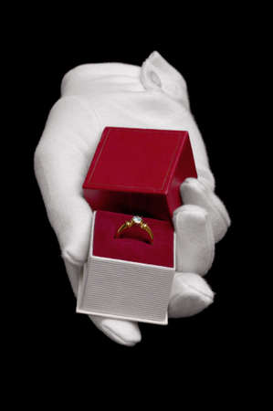 Hand wearing a white glove presenting a diamond ring in a proposal of marriage. Isolated on a black background. Stock Photo - 4181483