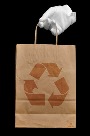 Hand in a white glove holding a brown recycled paper shopping bag with a recycling logo on it, isolated on black. All designs done by myself. Stock Photo - 4192766