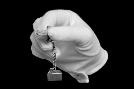 A hand in a white glove holding the key to a new house, isolated on black. Stock Photo - 4235161