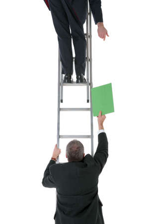Two businessmen on a ladder one passing a file to the other, isolated on a white background.