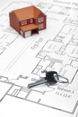 A model home and house key on architectural floor plans. photo