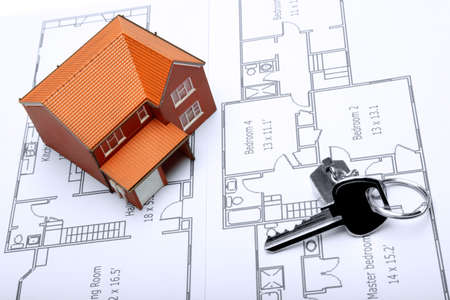 property development: A model home and house key on architectural floor plans for an extension.