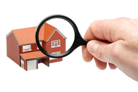 Examining a house through a magnifying glass isolated on a white background photo
