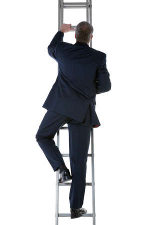 Rear view of a businessman wearing a blue suit climbing a ladder Stock Photo