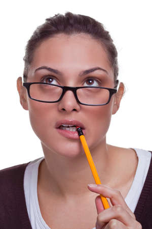 thinks: Attractive young female chewing a pencil as she thinks about something, white background.