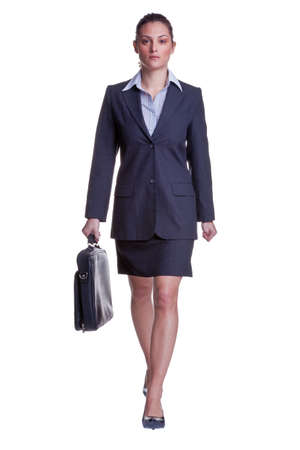 skirt suit: Businesswoman in suit walking towards carrying a briefcase, isolated on white background. Stock Photo