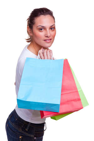 Attractive young female carrying colourful blank shopping bags over her shoulder, isolated on white background. photo
