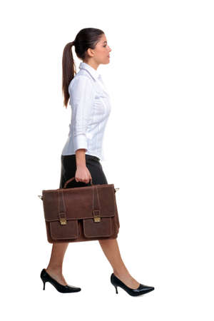 Young attractive businesswoman walking along carrying a brown leather briefcase, isolated on white background.