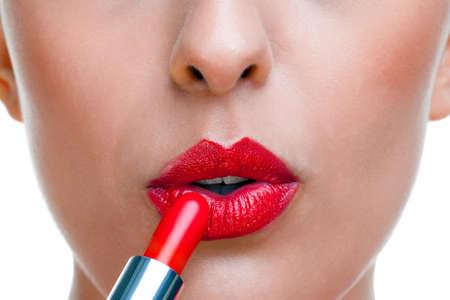 lapiz labial: Cerca de una mujer de la aplicaci�n de l�piz labial rojo, fondo blanco. Foto de archivo