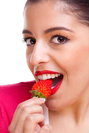 Head shot of an attractive female eating a strawberry, white background. photo