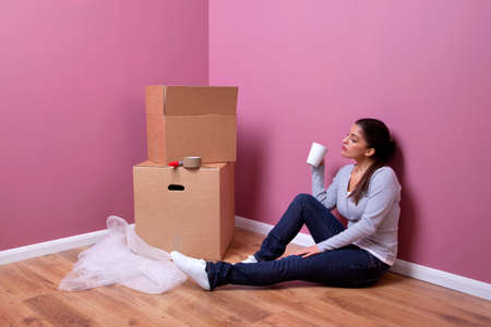 An attractive young woman takes a break during her house move