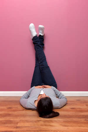 Female in casual clothing lying on the floor with her feet up against the wall