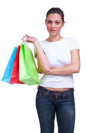 An attractive young woman waits arms folded with colourful shopping bags, isolated on a white background. Stock Photo - 4603957
