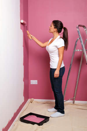 An attractive young woman decorating the wall of her new home