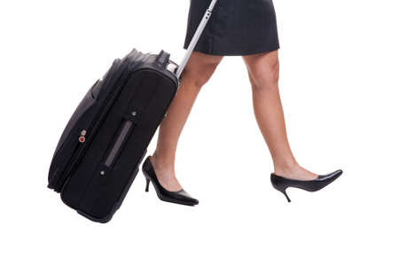 A businesswomans legs in short skirt pulling a suitcase, isolated on white background. photo
