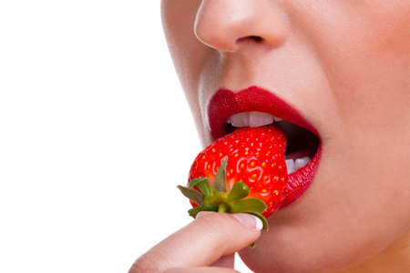 Close up of a woman wearing red lipstick eating a stawberry, white background. photo