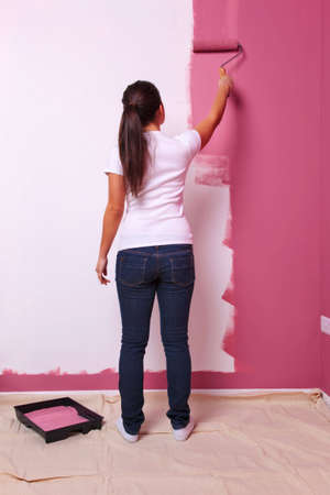 Young woman decorating the wall in her new home. photo