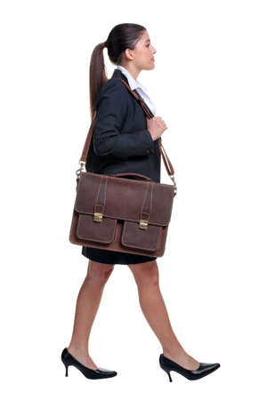 skirt suit: Businesswoman walking with briefcase over her shoulder, isolated on white background. Stock Photo