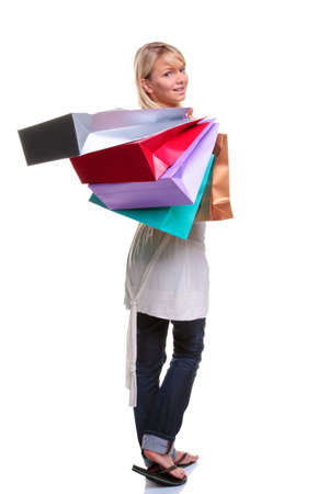 Beautiful young blonde woman carrying colourful shopping bags and looking back over her shoulder, isolated on white background photo