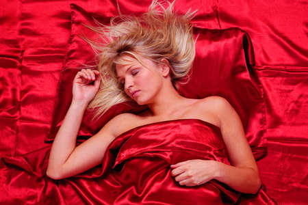 red pillows: Beautiful blonde woman asleep on red satin sheets