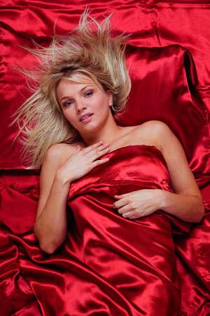 bedsheets: Una bella giovane donna bionda in un letto di seta rossa fogli, lavagna colpo.