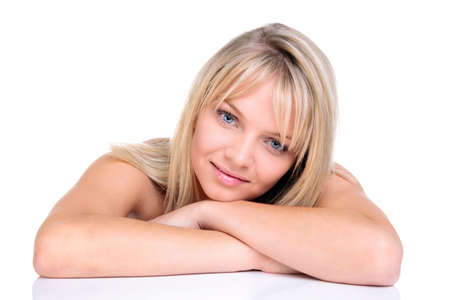 A beautiful blonde woman with her head resting on her arms, isolated on white background photo