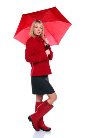 Beautiful young woman wearing a red coat and wellie boots holding a red umbrella, isolated on white background. photo