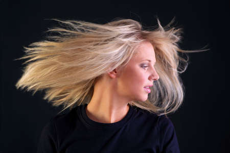 A beautful young woman with long blonde hairstyle  turning her head so her hair flows, black background.