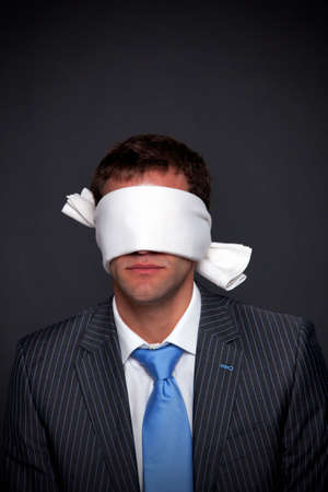 blindfolded: Businessman wearing a blindfold on a dark background with copy space.