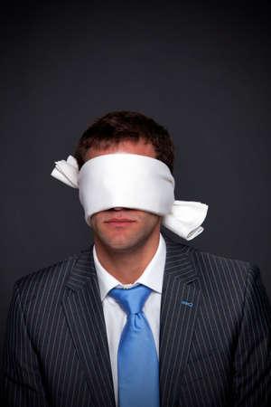 ojos vendados: Hombre de negocios el uso de una venda sobre un fondo oscuro con copia espacio. Foto de archivo