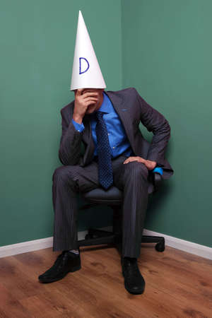 mistake: Businessman sat on a chair in the corner wearing a dunce hat