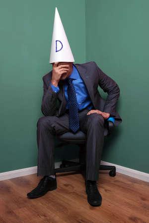 berisping: Zakenman zat op een stoel in de hoek het dragen van een hoed domkop